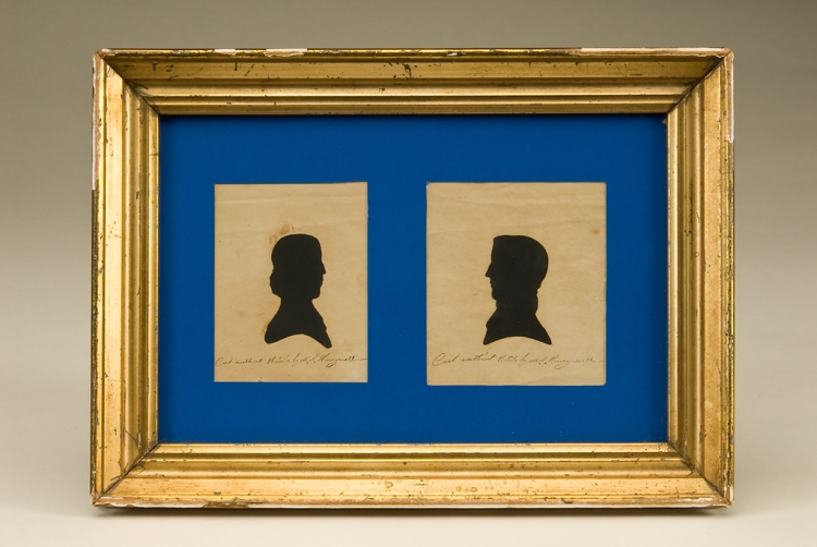 gold frame with blue paper. two paper cut silhouettes - man and woman facing each other