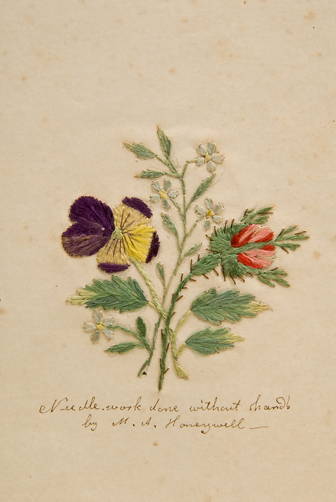 """Needlework - flowers, purple, yellow, and red. Signature says """"Needlework done without hands by M.A. Honeywell."""""""