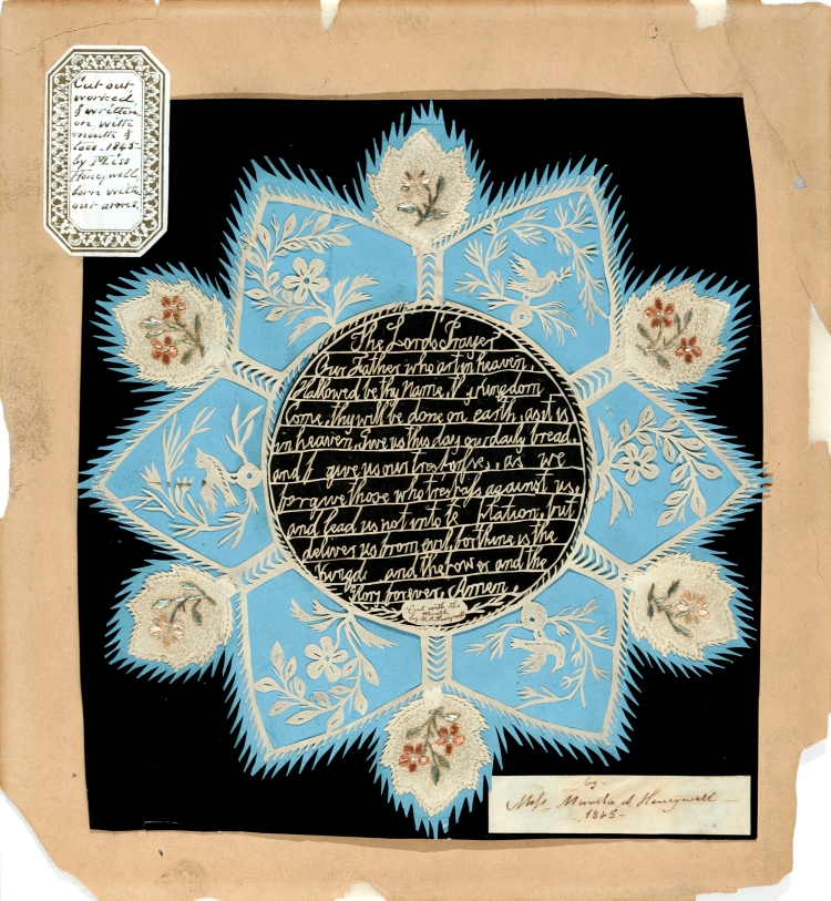 Paper cuts of Lord's Prayer in beige. Ornate flower border with blue trim mounted on black paper.